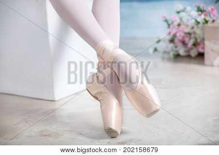 Young teenage ballerina is dancing and posing in the photostudio with blue and white walls