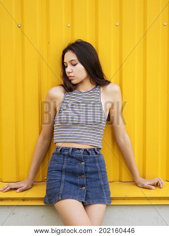 A close-up portrait of a confident trendy young girl wearing a striped T-shirt and denim skirt on an urban bright yellow wall background. A beautiful adolescence lady posing in the outdoors.