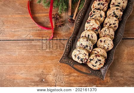 Christmas Cake Cookies on vitage plate with christmas tree branches and red rope on wooden background. Fruit cake cookies. Overhead view.