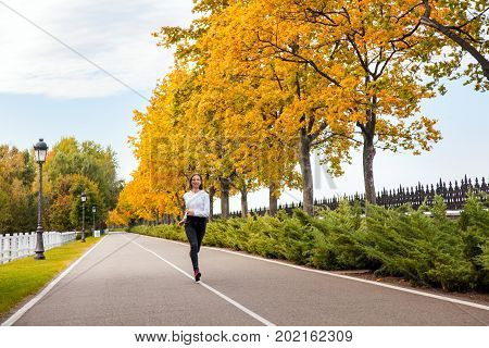 Happiness Young Adult Girl Jogging In Autumn Park, Looking At Camera And Toothy Smile.