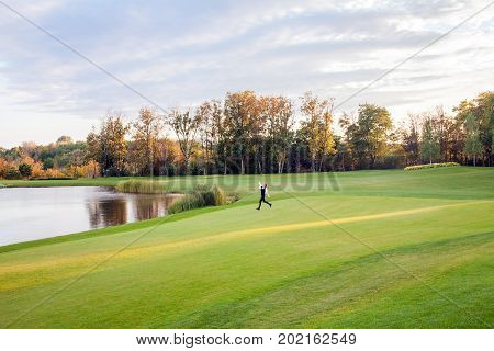 Autumn, Lake, Golf Course. Young Adult Girl Running On The Green Grass Of The Golf Course.
