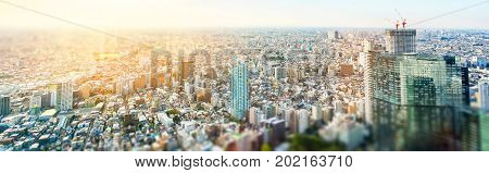 Business and culture concept - panoramic modern city skyline bird eye aerial view under dramatic sun and morning blue cloudy sky in Tokyo Japan. Miniature Tilt-shift effect