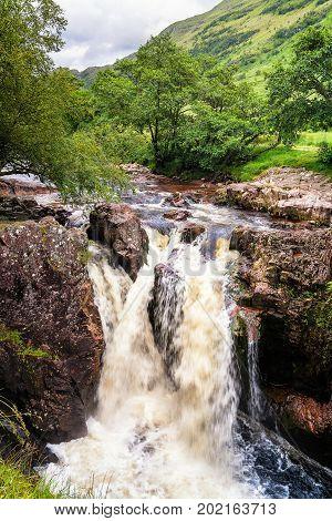 Waterfall falling between rocks in Glen Nevis Scotland United Kingdom. Cloudy rainy day.