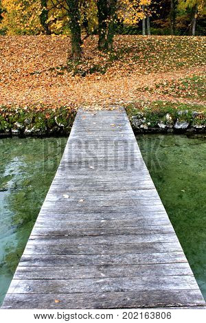 A wooden pier extends into a crystal clear alpine lake, Lake Annecy, where fishing boats dock in the city of Annecy in Autumn, France.