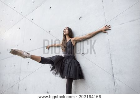 Cute ballerina with closed eyes leans on the textured concrete wall outdoors. Her right leg and arms are outstretched to the sides. Girl wears black dance wear with a tutu and light ballet shoes.