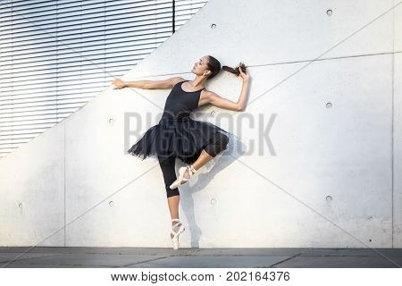 Gorgeous ballerina with closed eyes stands on the right toe and leans on the textured concrete wall outdoors. She holds one hand on the wall, other hand on the hair. Her left leg bent in the knee.