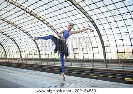 Wonderful ballerina is posing on the railway station. She stands on the right toe with outstretched to the side left arm and left leg and looks upward. Girl wears a blue dance wear with a black tutu.