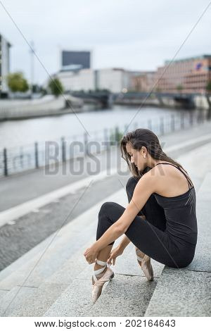 Ballerina sits on the stairs and dresses the ballet shoe on the background of the river embankment in the city. She wears a black top with leggings and light pointes. Vertical.