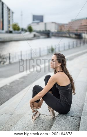 Dancer sits on the stairs and dresses the ballet shoe on the background of the river embankment in the city. She wears a black top with leggings and light pointes. Girl looks to the side. Vertical.