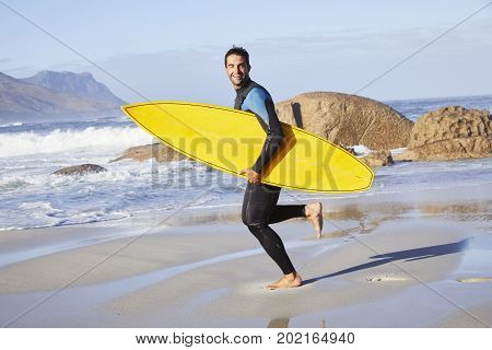 Surfer dude running with board on beach