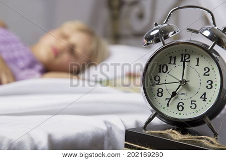 Alarm clock standing on bedside table. Wake up of an asleep young girl stopping alarm clock on a bed in the morning.
