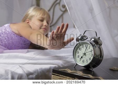 Early awakening. Wake up of an asleep young girl stopping alarm clock on a bed in the morning.