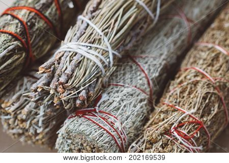 Close-up of the bandaged branches of dried herbs: sage, wormwood, pine and juniper