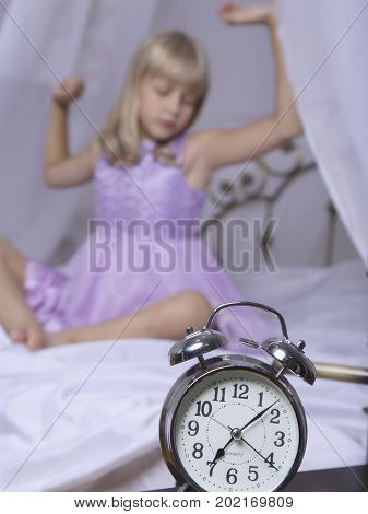 Alarm clock standing on bedside table. Wake up of an asleep young girl is stretching in bed in background.