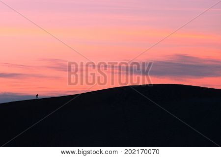 Lone person hiking on crest of huge sand dune black silhouette against warm colored sunset sky