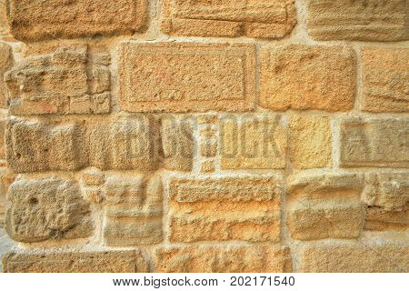 Wall fragment, old masonry, sand color background.