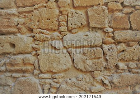 Ancient stone wall, masonry, abstract background, sand color.