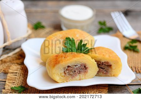 Fried ground beef and potato patties on a white plate. How to make potato patties stuffed with beef. Rustic style. Closeup