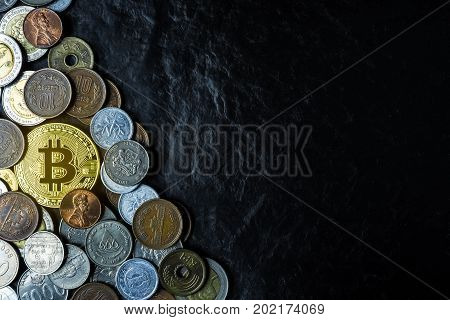 Golden bincoin with international money coins new currency among old currencies business and finance concept on black stone table background copy space