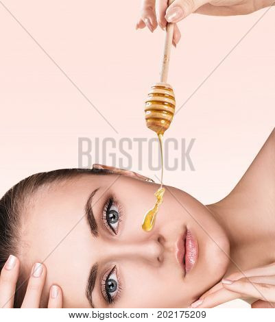 Honey flows down on woman's face from spoon. Honey therapy concept. Over beige background.