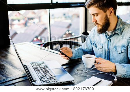 Man With Beard Using A Mobile Phone And Holding Coffee, Laptop Nearby