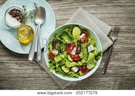 Green Salad with cheese and fresh vegetables on wooden background. Greek salad.