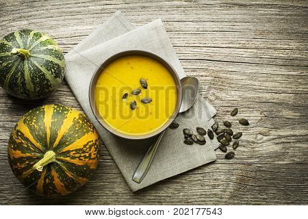 Bowl of fresh Pumpkin soup on wooden table