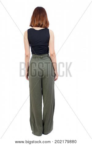 back view of standing young beautiful  woman.  girl  watching. Rear view people collection.  backside view of person. A girl in green trousers is standing with her hands down