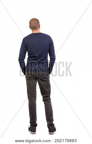 Back view of man in trousers. Standing young guy. Rear view people collection.  backside view person. Isolated over white background. man in black pants and sneakers is with his hands in his pockets
