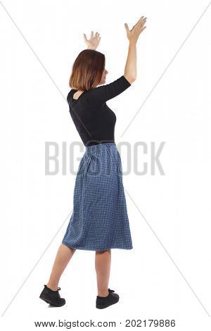 Back view of pointing woman in dress. beautiful girl. Rear view people collection.  backside view person. Isolated over white background. girl in blue skirt is standing indignantly with her hands up