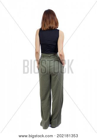 back view of standing young beautiful  woman.  girl  watching. Rear view people collection.  backside view of person. A girl in green trousers stands with her hands in her pockets.
