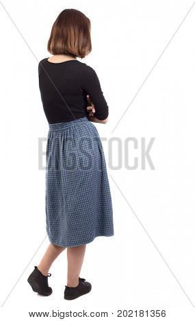 back view of standing young beautiful  woman.  girl  watching. Rear view people collection.  backside view of person. The girl in the blue skirt is standing sideways with her hands on her chest.