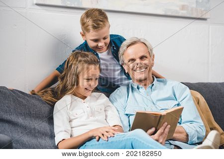 happy grandfather and grandchildren reading book while sitting on sofa at home