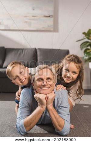 happy grandfather and grandchildren lying on floor and looking at camera