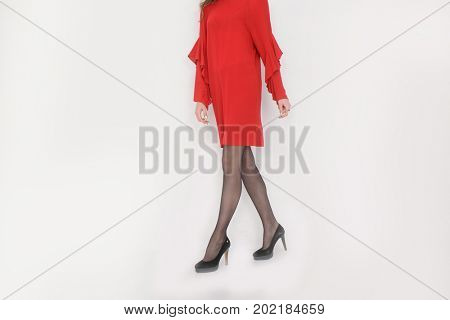 Woman in red sundress ..Perfect female legs in high heels posing