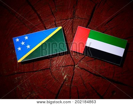 Solomon Islands Flag With United Arab Emirates Flag On A Tree Stump Isolated
