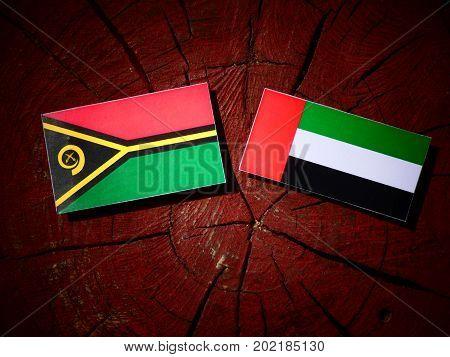 Vanuatu Flag With United Arab Emirates Flag On A Tree Stump Isolated