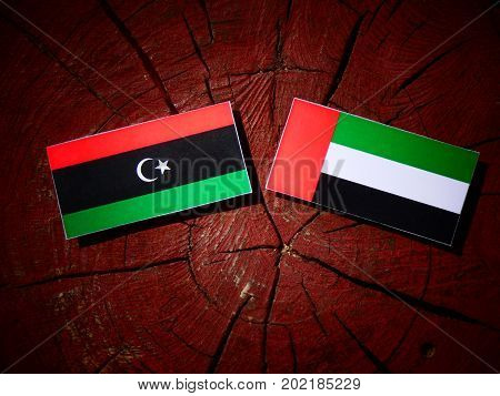 Libyan Flag With United Arab Emirates Flag On A Tree Stump Isolated