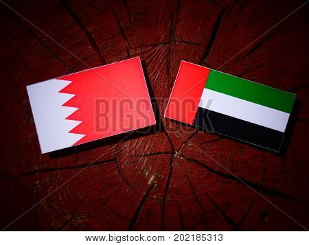 Bahraini Flag With United Arab Emirates Flag On A Tree Stump Isolated