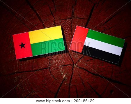 Guinea Bissau Flag With United Arab Emirates Flag On A Tree Stump Isolated
