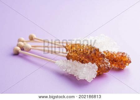 Crystalline sugar on wooden stick. Brown and white sugar. Refined and unrefined sugar.
