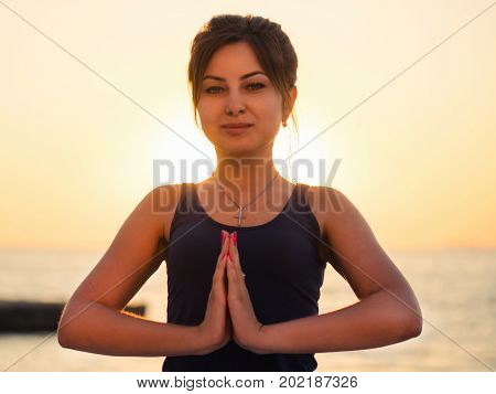 Fitness woman in sports clothing practicing yoga with namaste, meditating, breathing, relaxing sitting in the prayer position on the sea ocean beach, close up to water.