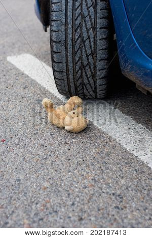 Toy bear in the blood under the car wheels