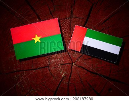 Burkina Faso Flag With United Arab Emirates Flag On A Tree Stump Isolated