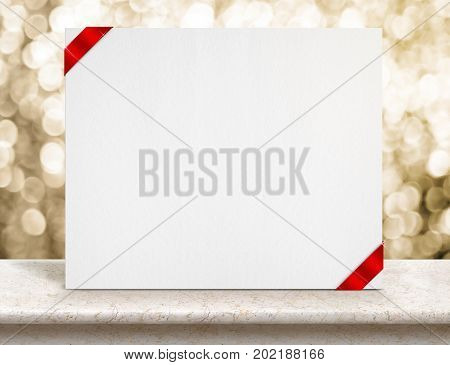 Blank White Paper Poster With Red Ribbon On Marble Table Top And Sparkling Gold Bokeh Light,mock Up