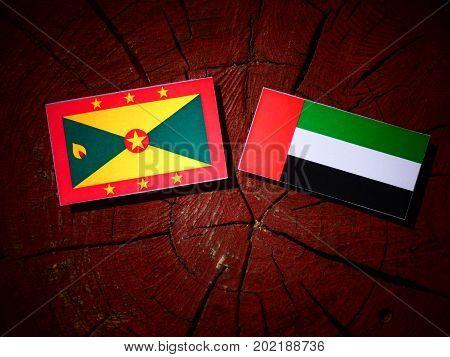Grenada Flag With United Arab Emirates Flag On A Tree Stump Isolated