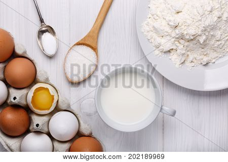 Ingredients for making pancake dough (eggs flour milk sugar salt) on white wooden table. Top view.