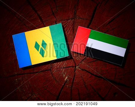 Saint Vincent And The Grenadines Flag With United Arab Emirates Flag On A Tree Stump Isolated