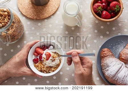 High angle view of unrecognizable young man enjoying delicious breakfast, fresh juicy strawberries, homemade croissants and corn flakes with milk and berries located on table