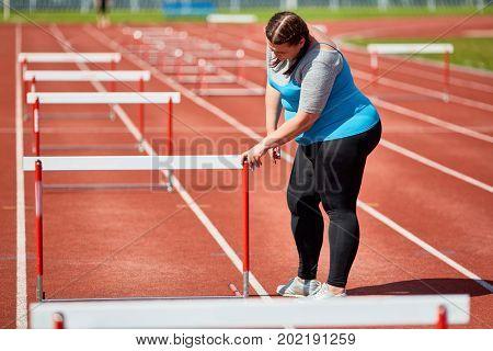 Ambitious plump female preparing for hurdle race on stadium